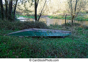 Boat in the reeds on river bank in forest