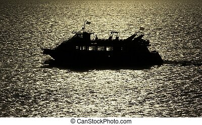 Boat in the Sun Strip - Recreational boat silhouetted in the...