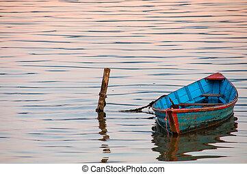 Boat in twilight water of Phewa Lake