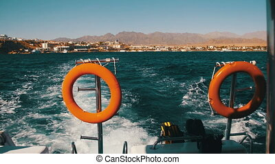 Boat is Floating on the Waves and Leaves a Trail in the Red Sea