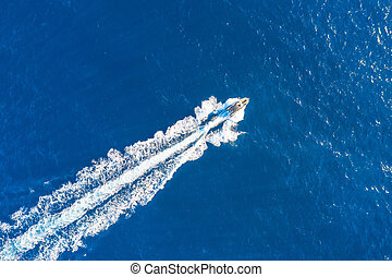 Boat launch at high speed floats in the Mediterranean, aerial top view.
