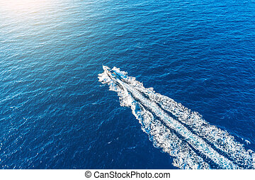 Boat launch at high speed floats to sunlight in the Mediterranean, aerial top view.