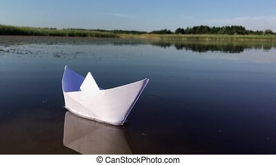 Boat made of paper floating on the river