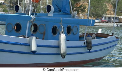 Boat Moored in Harbor - Old blue wood fishing motorized boat...