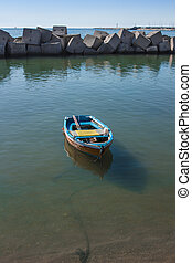 Boat moored in the port of Salerno in a sea green waters.