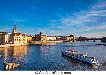 Boat navigating on Vltava river at sunset in Prague