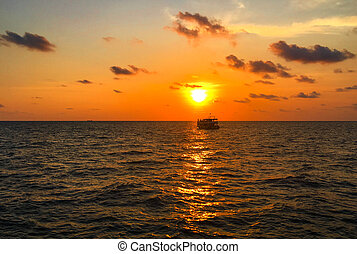 Boat on a calm sea in tropical sunset