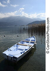Boat on Annecy lake and mountains, landscape in Savoy
