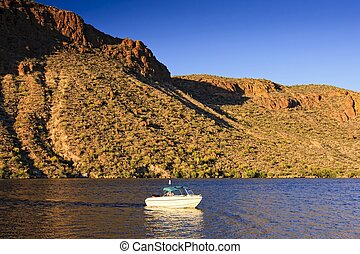 Fishing boat on Canyon Lake in central Arizona surrounded by the beauty of the desert.