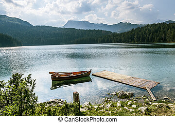 boat on Black Lake in the national park Durmitor and mountains in the background.
