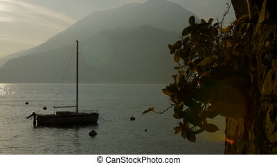 Boat on Lake Como at the sunset. Silver linings in Lake Como at the sunset.