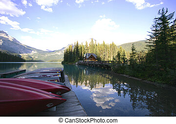 A dock of boats on a tranquil mountain lake with a small cabin in the background.