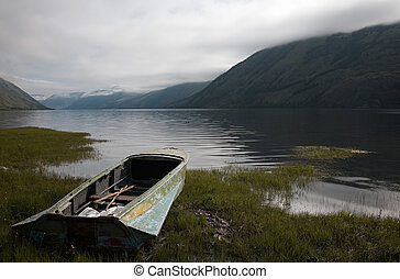 Boat on the bank of mountain lake
