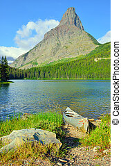boat on the bank of the Swiftcurrent lake in high alpine...