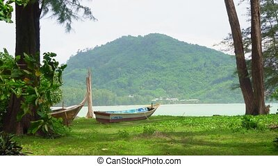 boat on the beach on a tropical island. in the shade of trees.