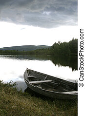 Boat on the Lake - An extremely old boat sitting quietly on...