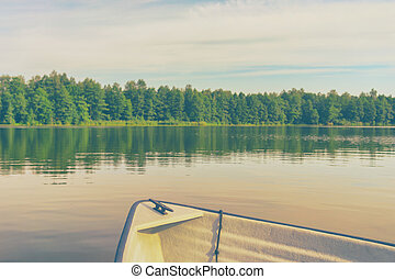 Boat on the lake in the background of the forest