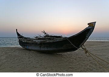 boat on the ocean shore at sunset. Kerala, India