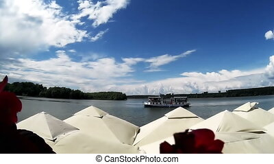 Boat on the river with white fluffy clouds moving over it...
