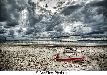 boat on the sand under a dramatic sky
