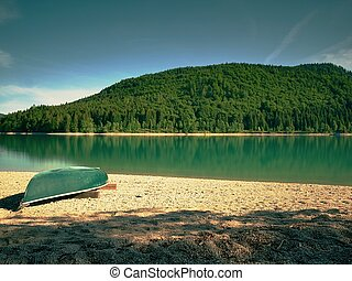 Boat on the shore of a smooth lake in early summer. Beautiful lake