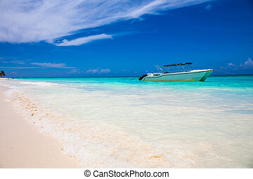 boat on tropical beach with blue water background