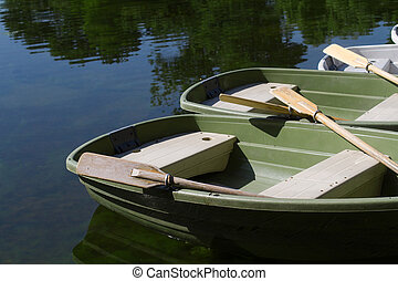 boat parked on the shore of a lake with their oars up