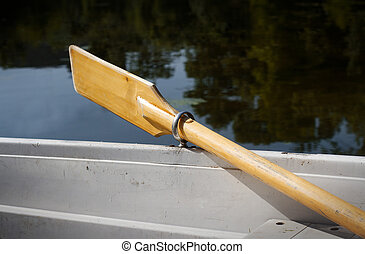 boat parked on the shore of a lake with oars up