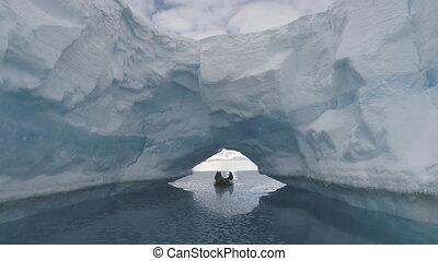 Boat passes through iceberg arch. Antarctica. - Zodiac Boat...