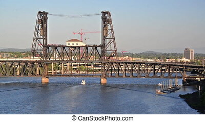 Steel Bridge in Portland, Oregon with a boat passing under it