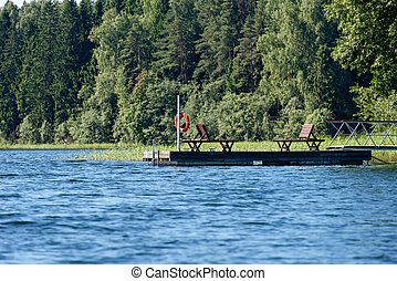Boat pier with deck chairs on a forest lake