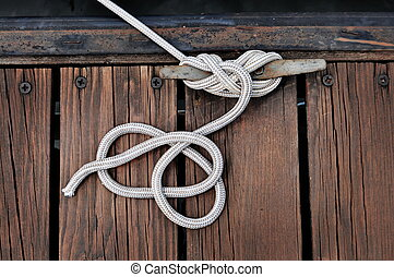 Boat Rope - white rope securing boat to wooded dock