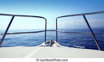 boat sailing in a calm blue sea mediterranean water from bow deck