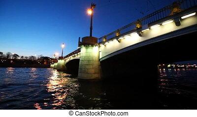 Boat sails under Ushakovsky Bridge illuminated at night