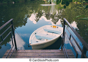 boat stand on a forest lake during the peak of summer in mountains.