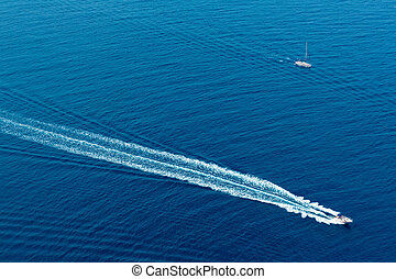 Boat surf foam aerial from prop wash in blue sea