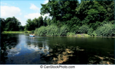 couple floating in a rowing boat on the lake, effects: fast playback, tilt shift,