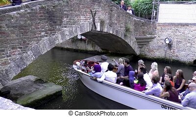 Tourists take a boat tour along the canals in Bruges, West Flanders, Belgium, CIRCA July 2017.