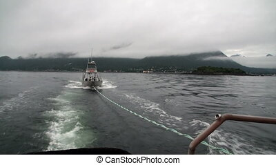 Boat tow in fog on water of Pacific Ocean on background mountains Alaska.