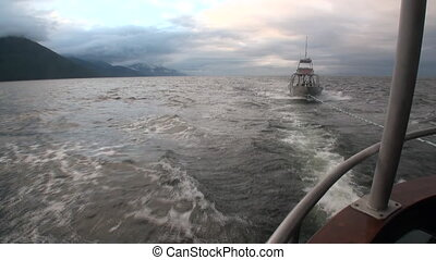Boat tow on water of Pacific Ocean on background mountains in Alaska.