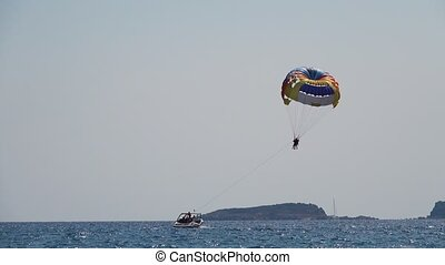 Boat tows a couple on a parachute over the sea, enjoying a...