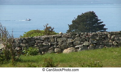 Boat Travelling on Sea Near Stone Wall