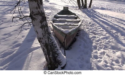 boat under snow in winter near river