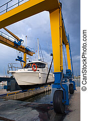 Boat wheel crane elevating motorboat to yearly paint