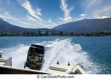 Boat white wake on the blue lake of Annecy, France