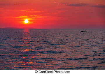 Boat with a fisherman on calm sea at sunset near the island of C