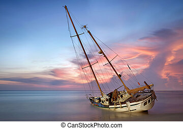 boat wreck - sailboat wreck in sea on the sand beach at...