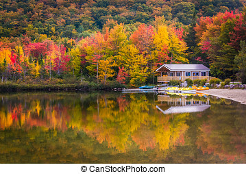 Boathouse and fall colors reflecting in Echo Lake, in Franconia