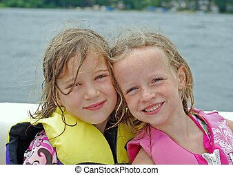 boating buddies - two girlfriends show their affection while...