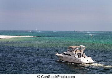 Cabin cruiser motors through the waters of Destin Pass, Florida.
